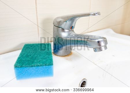 Blue sponge for washing dirty faucet with limescale, calcified water tap with lime scale on washbowl in bathroom, house cleaning concept stock photo