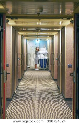 Cleaners trolley with cleaning equipments at hotel in hallway . Cleaning cart with cleaning equipment at the hotel in corridor. View of the hotel corridor. stock photo