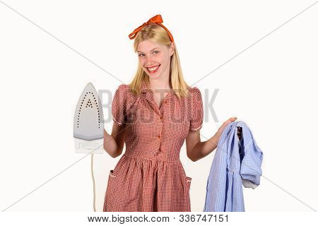 Housekeeper woman in uniform with iron in hand. Girl holding iron in hand. Beautiful woman holds steam iron. Housework and household concept - housewife ironing clothes. Retro woman ironing clothing. stock photo