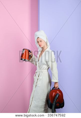 Serious sexy woman with vacuum cleaner and kettle. Busy woman with vacuum cleaner and kettle at home. Housewife with vacuum cleaner and electric kettle in hands. Woman in bathrobe and towel on head. stock photo