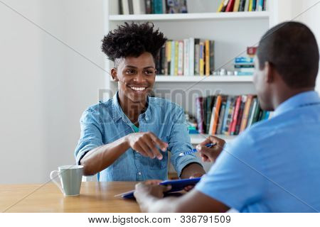 Laughing african american apprentice signing contract at office stock photo