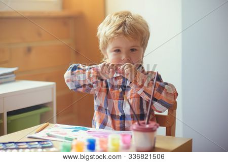 Felt-tip pens. Tools for drawing. A beautiful child in a kindergarten draws a picture for mother. Creative education. Art for children. Game and drawing. School of drawing. Handsome boy at table. stock photo
