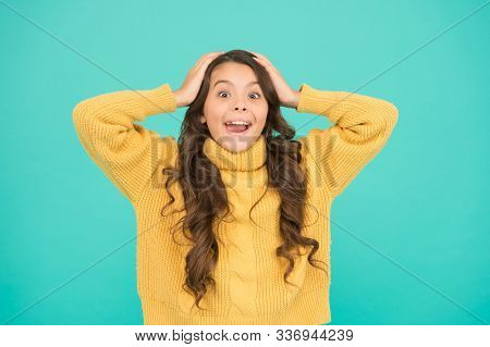 Adorable surprised girl wear yellow sweater turquoise background. Surprise concept. Good vibes. Emotional baby. Surprised child. Positive attitude to life. Kids psychology. Feeling surprised. stock photo