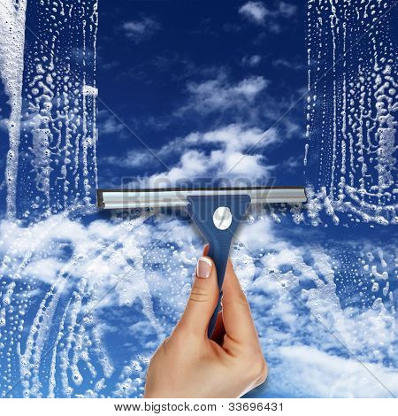 Hand cleaning window with blue sky and white clouds stock photo
