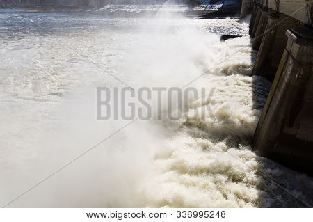 Water drains from the reservoir creating pillars of water vapor and foam. A hydroelectric power station generates electricity, draining excess water from reservoir into a river. Waterfall on the river stock photo