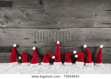 Wooden christmas background with red santa hats for a festive frame or card.