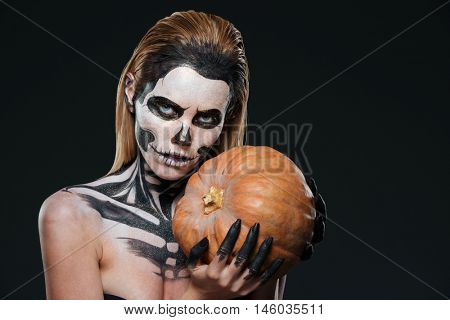 Woman with skeleton halloween makeup holding pumpkin over black background