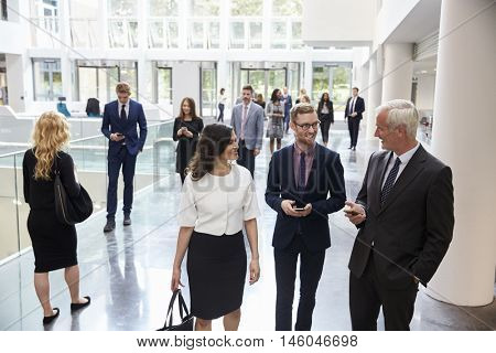 Businesspeople In Busy Lobby Area Of Modern Office stock photo