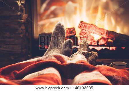 Cold fall or winter evening. People resting by the fire with blanket and tea. Closeup photo of feet
