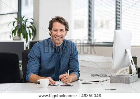 Cheerful young businessman working at desk in office. Successful business man sitting in office with