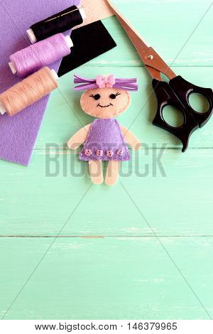 Handmade doll, scissors, thread set, needle, felt sheets on wooden background with copy space for text. How simply and cheaply make a kids toy. Cute doll crafts with felt for kids stock photo
