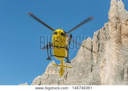 Medical rescue helicopter flying rescue injured climber on the Tre Cime. Italy, Dolomites stock photo