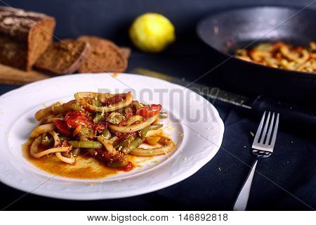 Calamar with tomato and chilli sauce in white dish on dark wood background. Plate with dish and bread on bacground stock photo