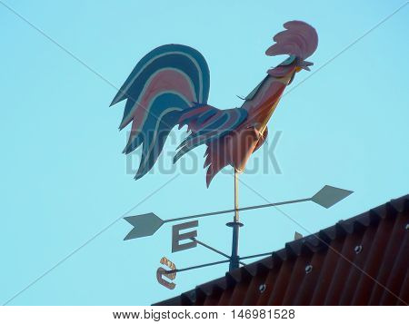 weathervane on roof of metal house to determine wind direction in form stock photo