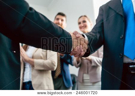 Close-up of the handshake of two business men in the applauses of three happy employees, after an important agreement for the success of the company stock photo