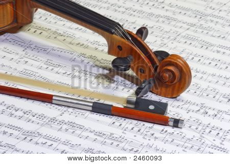 Violine head close-up with bow over music notes stock photo