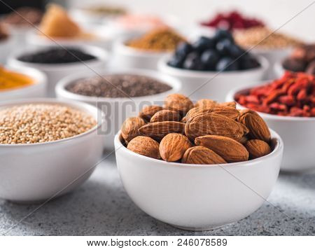 Almond in small white bowl and other superfoods on background. Selective focus. Different superfoods ingredients. Concept and illustration for superfood and detox food stock photo