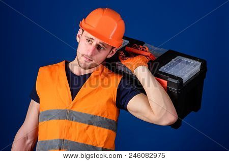Repair and renovation concept. Worker, repairer, repairman, strong builder on thoughtful face carries toolbox on shoulder, ready to work. Man in helmet, hard hat holds toolbox, blue background. stock photo