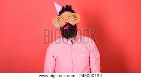Man with beard on calm face with party horn, red background. Guy in party hat with holiday attributes celebrates. Surprise concept. Hipster in giant glasses blows into party horn. stock photo