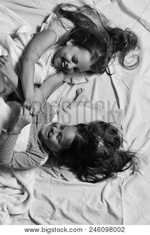 Schoolgirls in pajamas wallow on colorful pillows, top view. Kids with happy faces have fun lying in bed. Childhood and friendship concept. Girls lie on white and pink bed sheets fighting. stock photo