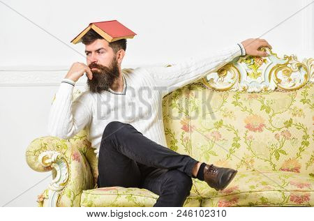 Macho sits with open book on head, like roof. Boring literature concept. Guy bored, fed up of reading old boring book. Man with beard and mustache sits on baroque style sofa, white wall background. stock photo