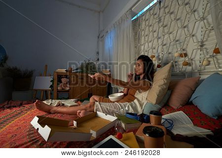 Pretty Vietnamese college student eating snacks and watching tv late at night stock photo