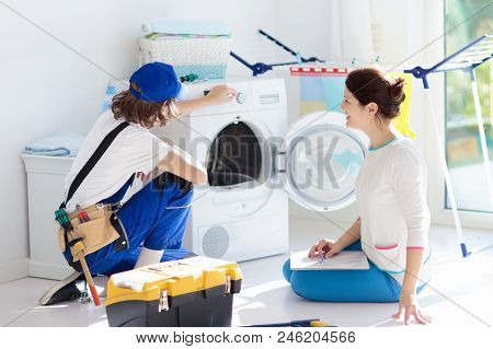 Washing machine repair service. Young technician examining and repairing tumble dryer. Woman looking at broken household appliance. Plumber with customer. Man fixing washer. stock photo
