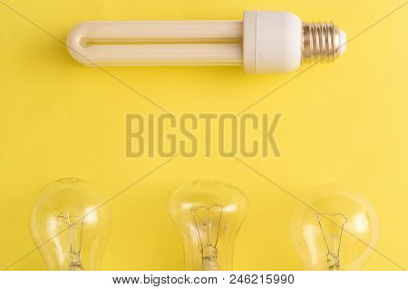 Energy-saving Lamp vs. incandescent lamps. The concept of energy saving . On a yellow background.One energy-saving bulb corresponds to three incandescent bulbs.Location of energy-saving lamp on top. stock photo