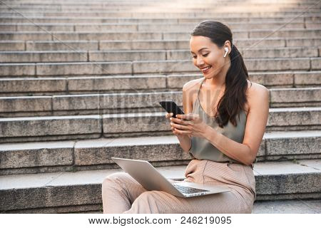 Image of pleased smiling woman 20s wearing casual summer outfit and bluetooth earpod sitting on street stairs and holding smartphone while using silver laptop stock photo