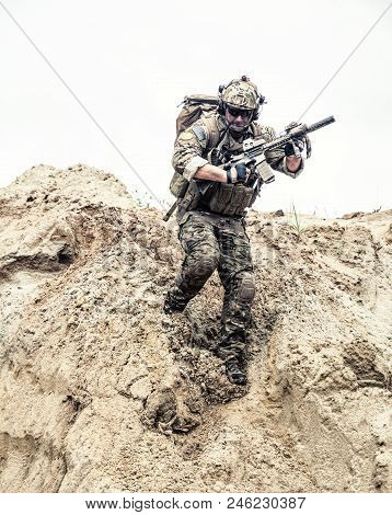 United States army commando, special forces infantry armed with assault rifle in combat uniform and load carrier, descending from steep sand dune. Armed conflict in desert, soldier rush across dunes stock photo