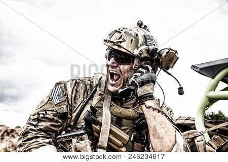 Special forces soldier, military communications operator or maintainer in helmet and glasses, screaming in radio during battle in desert. Calling up reinforcements, reporting situation on battlefield stock photo