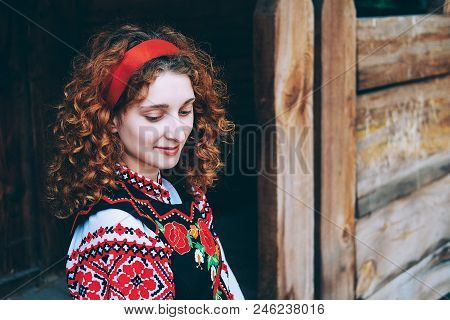 Young Slavonic woman in traditional embroidered costume and red shoes sitting on the porch stock photo