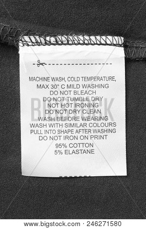 Care and composition clothes label on black textile background closeup stock photo