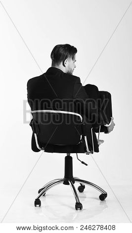 Businessman thinks about solutions isolated on white background. Man in smart suit looks for new ideas. Business, solutions and creative thinking concept. Office worker rolling in chair back view. stock photo