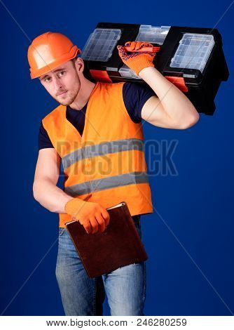 Worker, repairer, repairman, builder on calm face carries toolbox on shoulder, ready to work. Repair service concept. Man in helmet, hard hat holds toolbox and folder with documents, blue background. stock photo