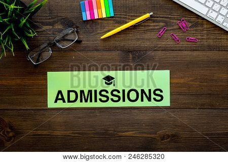 College admission concept. Word admissions with graduation cap sign on student desk with computer top view. stock photo