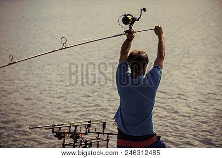 Spin fishing, angling, catching fish. Hobby, vacation, pastime. Fisherman cast fishing rod in lake or river water. Man fish with spinning tackle on summer day. Adventure, sport, activity. stock photo