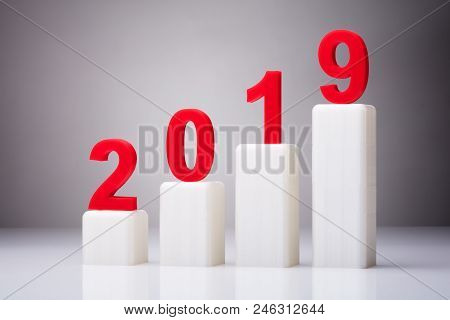 Year 2019 With Increasing Arrow Against Gray Background stock photo