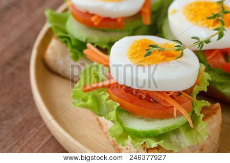 Open faced sandwich with toast lettuce tomato carrot cucumber and boil egg. Grilled sandwich on wooden plate in close up view. Delicious open sandwich for breakfast for family served on wood table. Homemade and healthy food concept of sandwich. stock photo