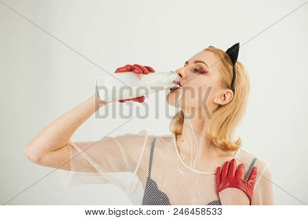 Girl in red latex gloves catsuit licking milk like cat, over white background stock photo