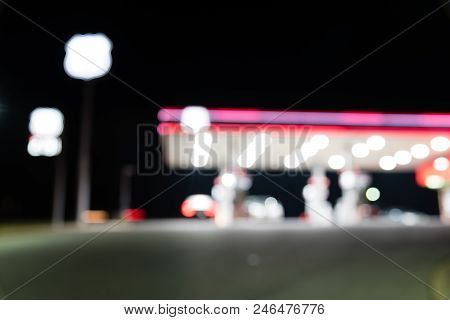 Blurred image of gas station with car refueling at night. Defocused, out of focus gas station and convenience store in twilight. Abstract blur petrol station background with copy space. stock photo