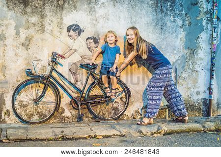 Georgetown, Penang, Malaysia - April 20, 2018: Mother and son on a bicycle. Public street art Name Children on a bicycle painted 3D on the wall that's two little Chinese girls riding bicycle in Georgetown, Penang, Malaysia. stock photo