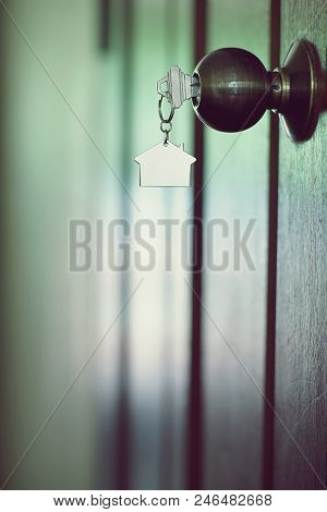 Home key with metal house keychain in keyhole, property concept stock photo