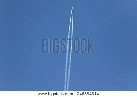 One plane leaves contrails trace in a clear blue sky. Airplane vapour trails. stock photo