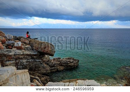 A woman alone rests on the rocks on the beach. She dreams about the future and looks into the distance. Dreams Come True. stock photo