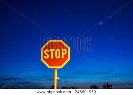 Stop Sign In The Night City. Traffic Regulation. Blue Sky.