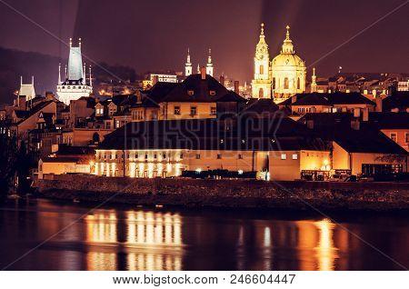 Lesser town bridge tower, Strahov monastery, St. Nicholas Church and Vltava river in Prague, Czech republic. Night scene. Travel destination. Red photo filter. stock photo