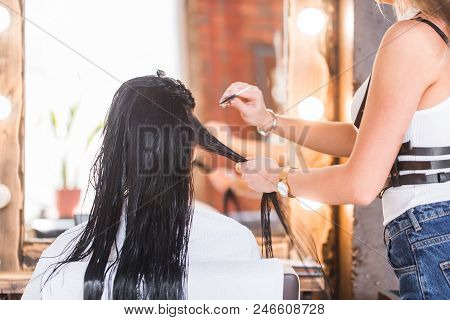 Female hairdresser hold in hand lock of hair, scissors closeup. Keratin restoration, latest trend, fresh idea, haircut picking, shorten tips concept stock photo