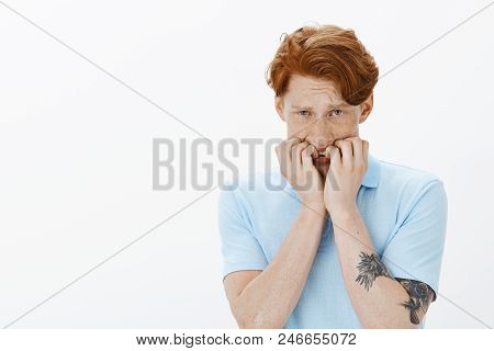 Guy wants to mommy. Portrait of scared trembling timid guy with red hair and freckles, biting fingernails, frowning, feeling anxious and horrified, shaking from fear and standing over gray background. stock photo