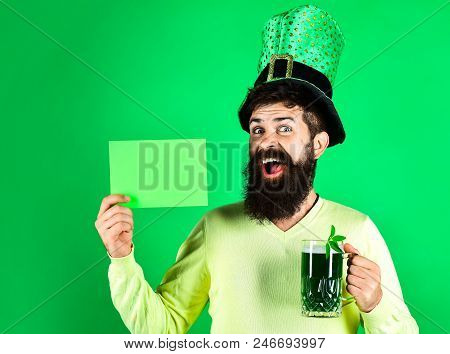 Saint Patrick's Day symbols. Bearded man in green hat holds green board. St Patrick's Day. Happy four leafed clover. Green hat with clover. Patricks Day green shamrock. Ireland tradition. stock photo